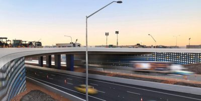 This is a photograph of the major project overpass over the freeway that Monford Group completed. The cars traveling underneath are blurred from the speed they are traveling. Artwork decorates the sides of the large infrastructure..
