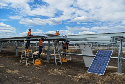 This photograph is of a solar panel installation team installing a solar panel at the solar farm during a sunny day.